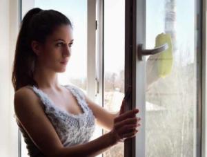 chica limpiando ventana