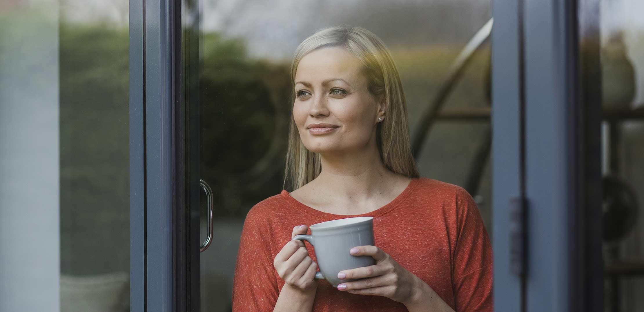 Mujer mirando ventana aluminio